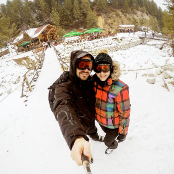 Attractive couple taking awesome selfie with a wooden cabin covered in snow in the background.